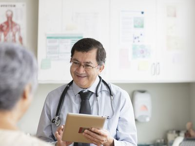 Hispanic doctor with digital tablet talking to patient