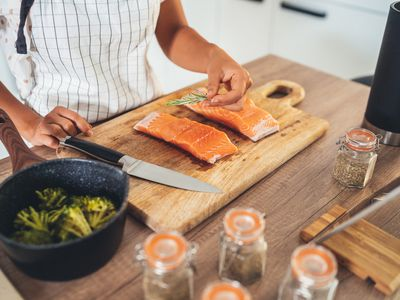Slicing salmon on a cutting board while preparing a meal