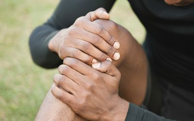 a picture of a man holding injured knee.