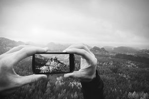 Man takes photo with phone on rock empire