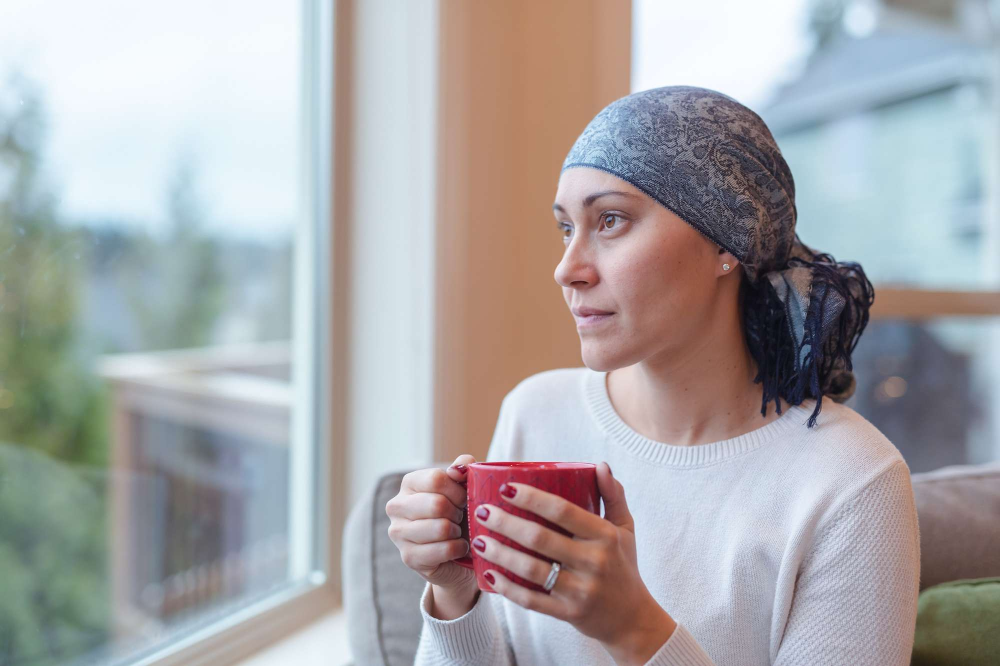 A woman with head scarf on looking out the window