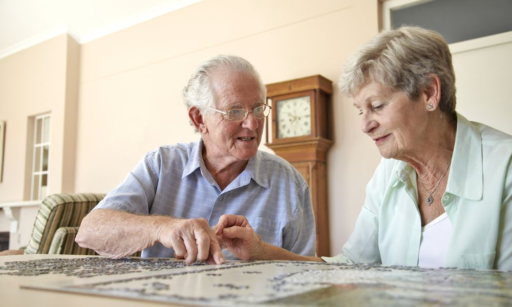 Elderly couple doing jigsaw puzzle