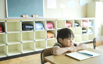 Schoolboy (4-5) sitting by desk in classroom