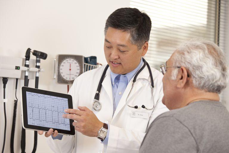 Doctor using digital tablet to talk to senior man