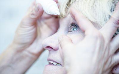 woman putting eye drops in