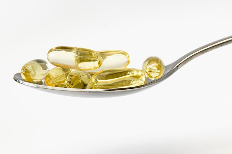 Spoon full of omega 3 capsules against white background indicating health and well-being.