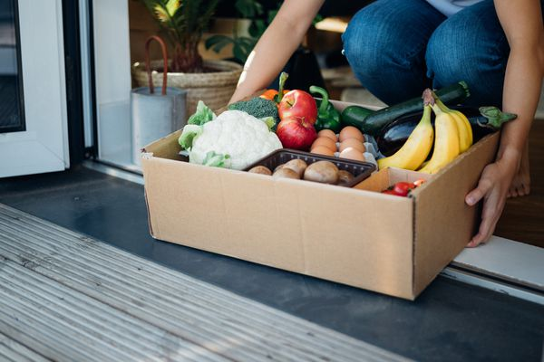 fruits and vegetables in a box at a doorstep