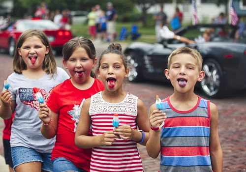 Children sticking out tongues dyed red and blue from their ice pop during Fourth of July parade