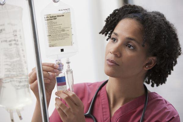African nurse preparing IV drip - stock photo