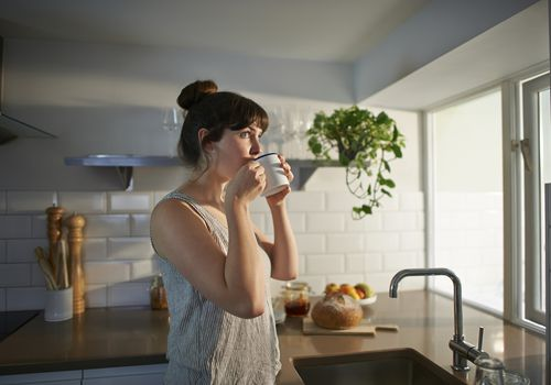 A woman standing in her kitchen drinks from a mug.