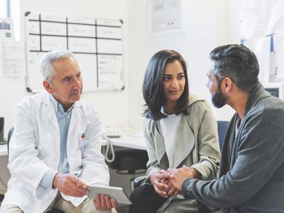 Doctor discussing over digital tablet with couple