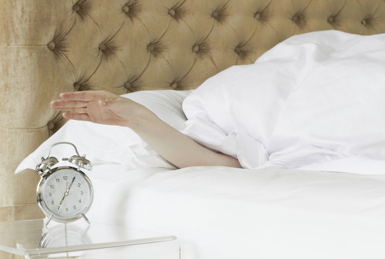 woman reaching her arm out from under bed covers to turn off alarm clock