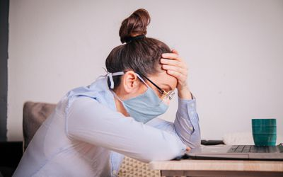 woman with a mask on in front of laptop