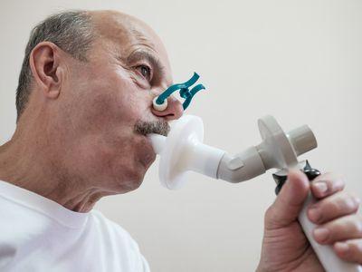 Man uses spirometer for pulmonary function testing