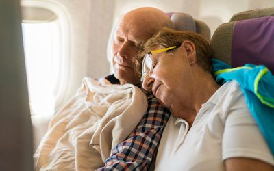 Senior couple sleeping in an airplane