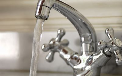 Close up of water faucet running