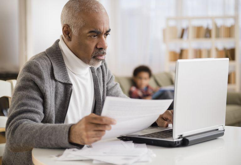Mixed race man paying bills on laptop