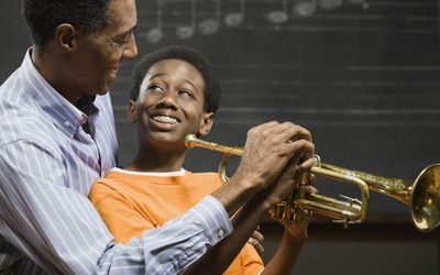 A man teaching a boy how to play the trumpet