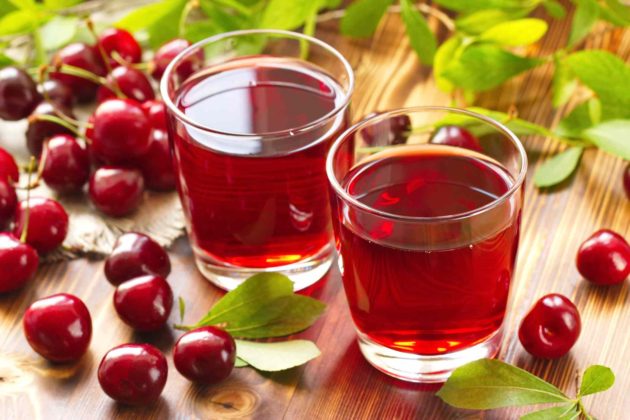 Two glasses of cherry juice surrounded by whole cherries.