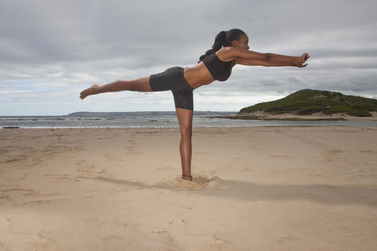 Photo of woman practicing yoga on the beach.