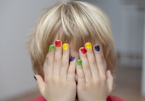 Hands with colorful painted nails in front of a young boy's face
