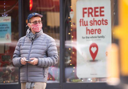 Man standing by flu shot sign.