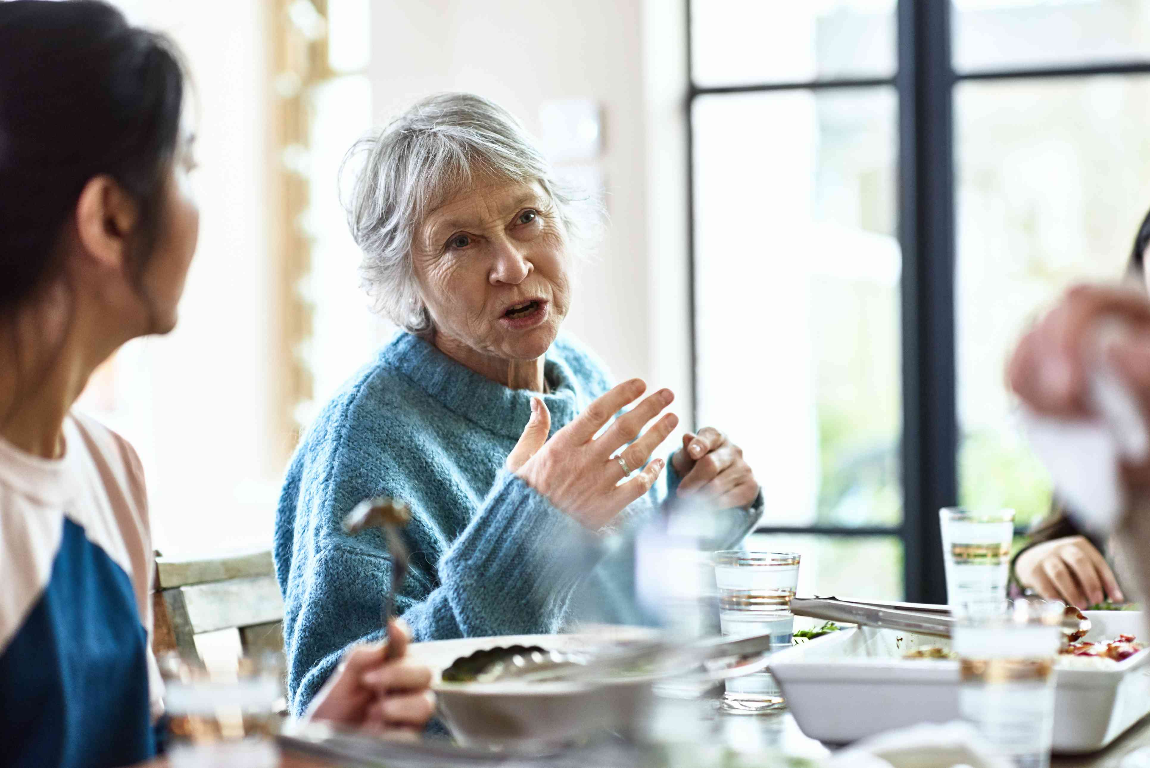 Woman talking and gesturing at dinner party
