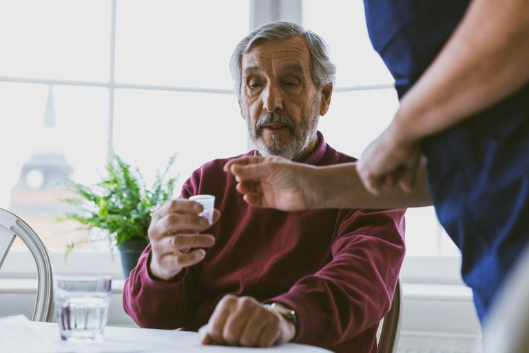 Midsection of caretaker giving medicine to senior man at home