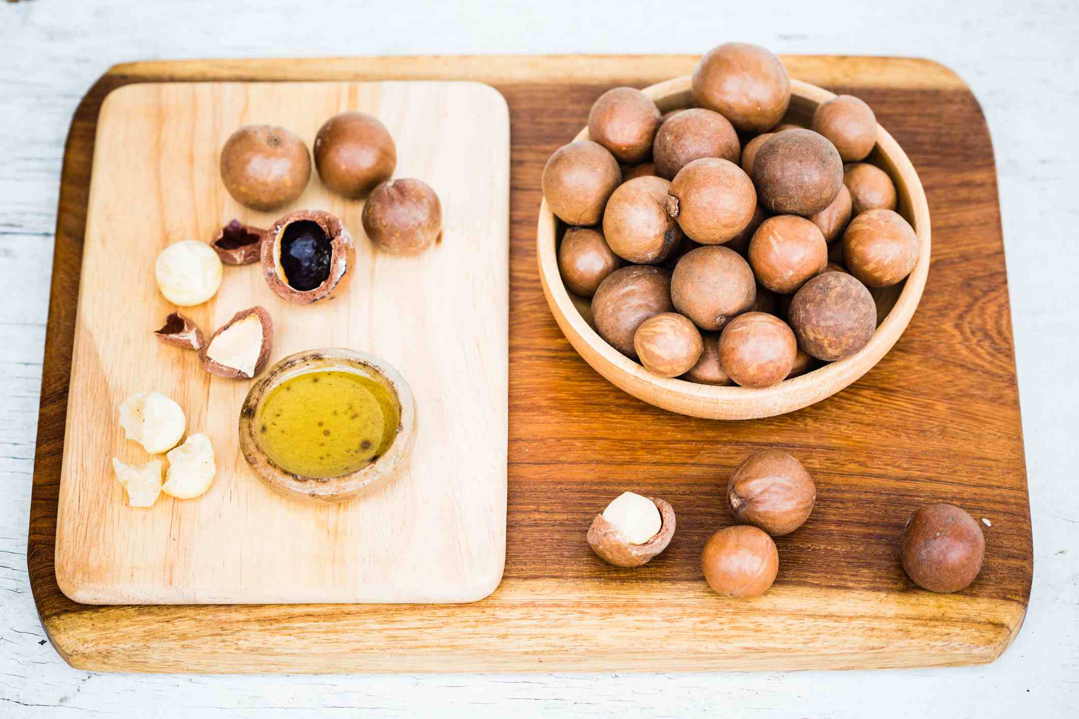 Macadamia nuts and oil on cutting board