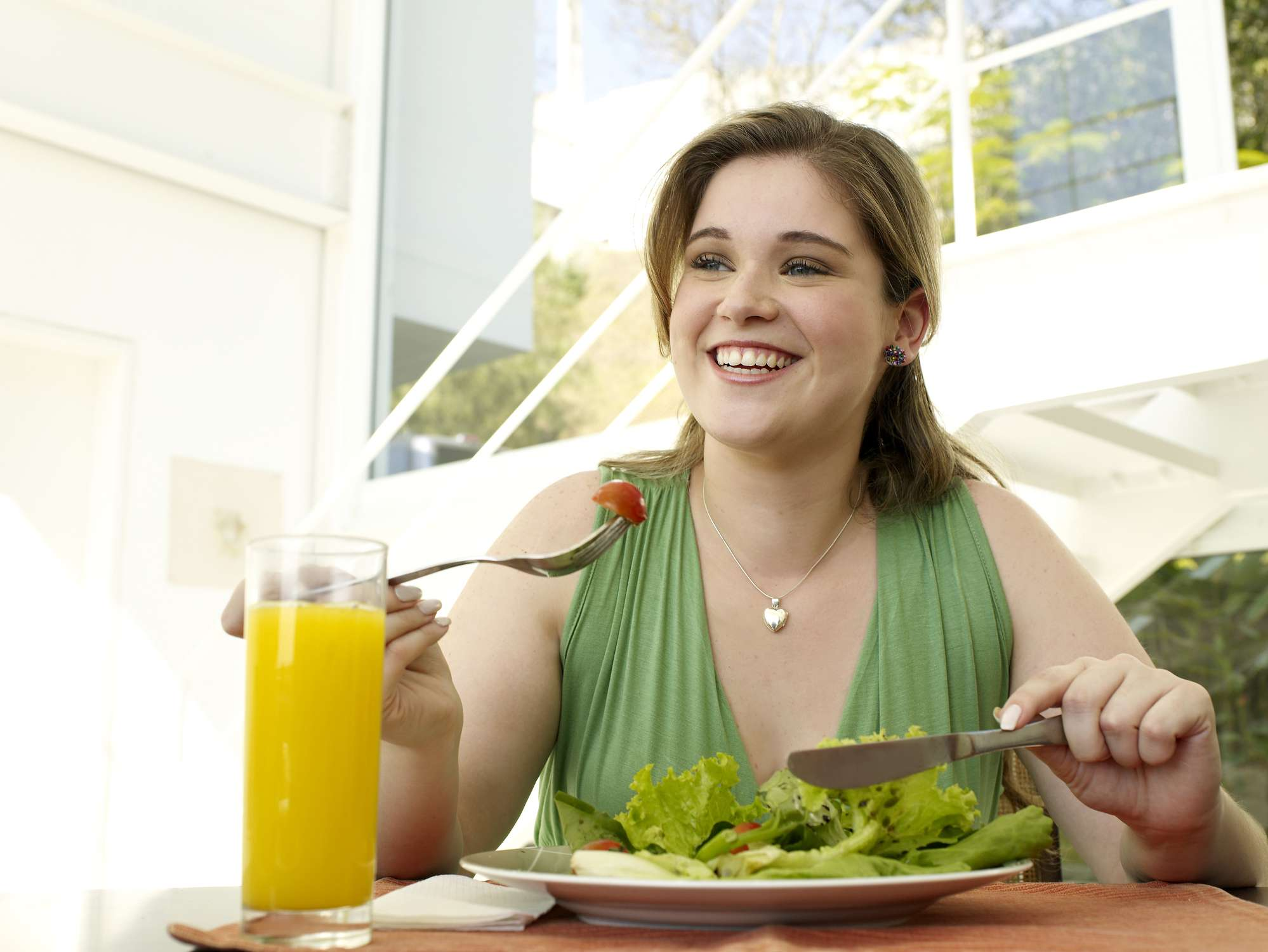 A woman eating a salad in the daytime