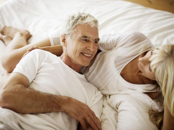 An older couple laying in bed together