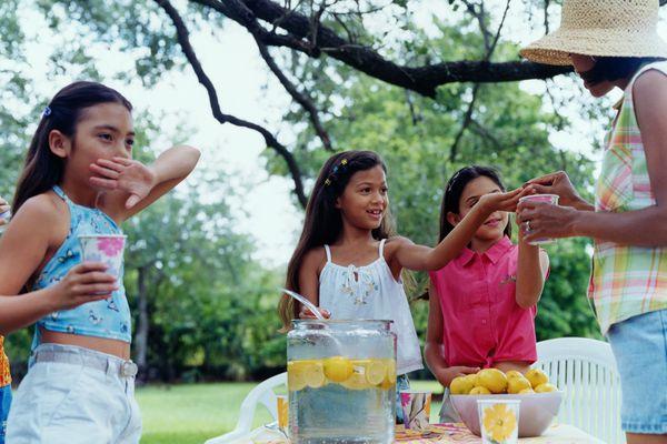Girls (6-8) selling lemonade on lawn