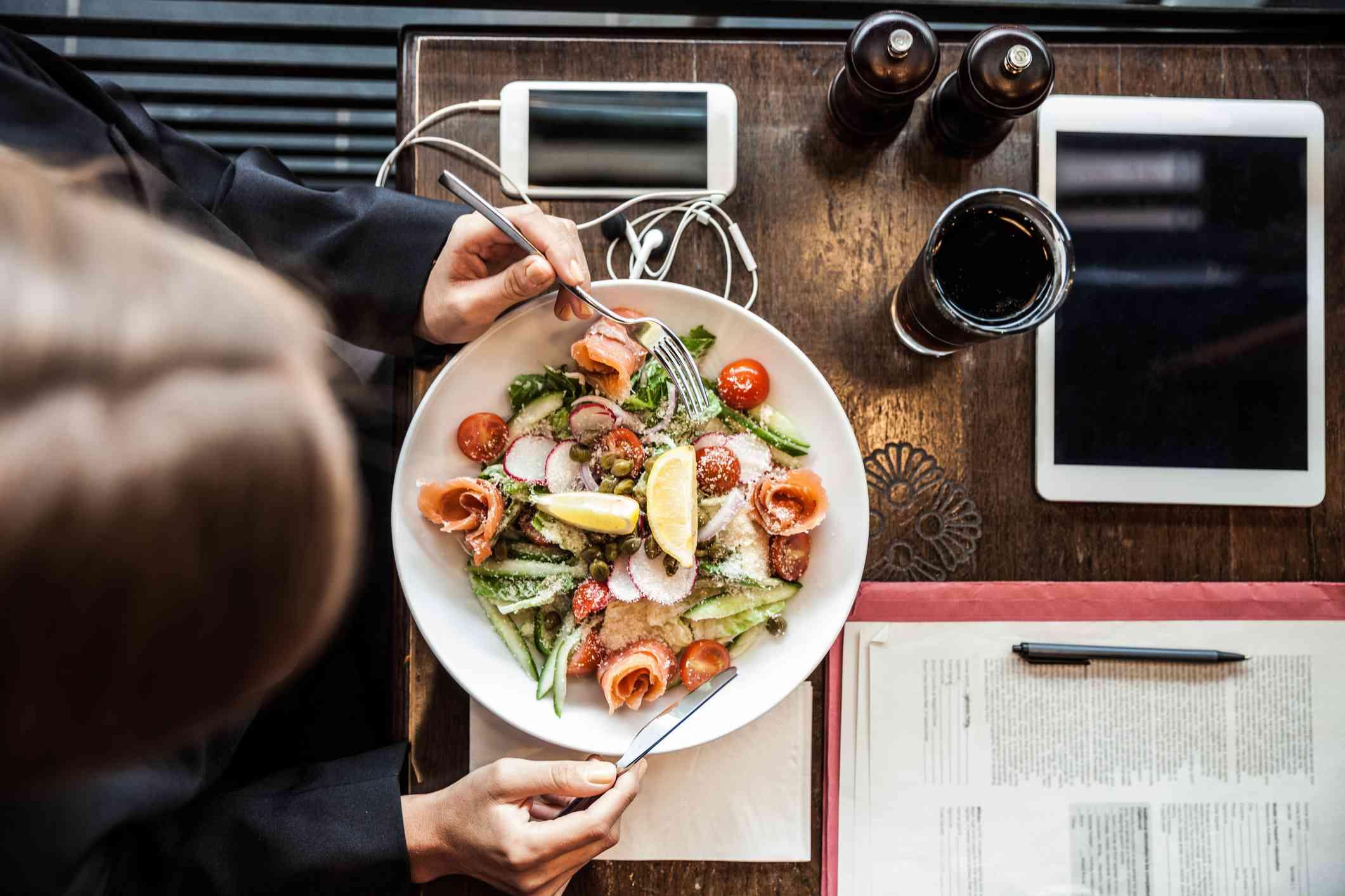Woman eating healthy salad at restaurant