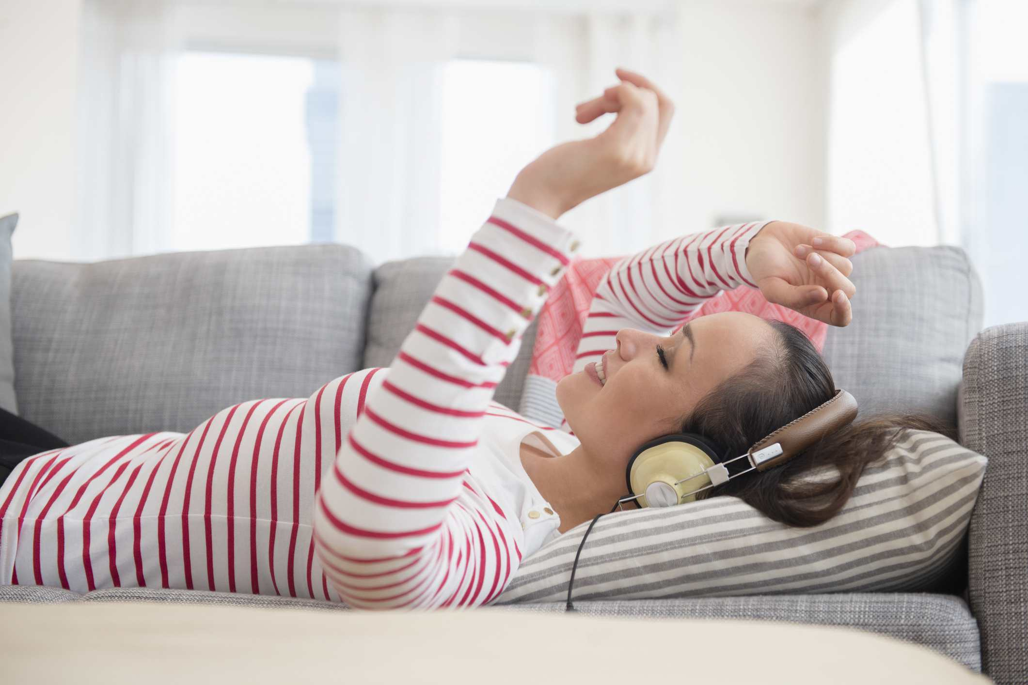 Woman lying on couch listens to headphones.