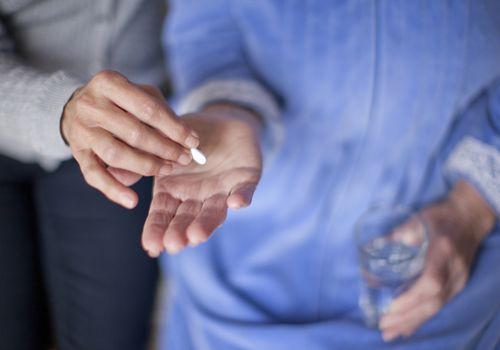 woman giving senior a pill to take with water