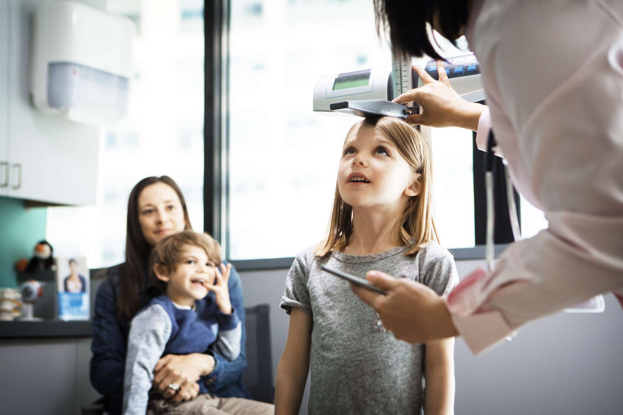Doctor measuring girls height while family sitting at clinic
