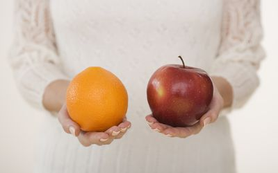 Close up of woman holding apple and orange