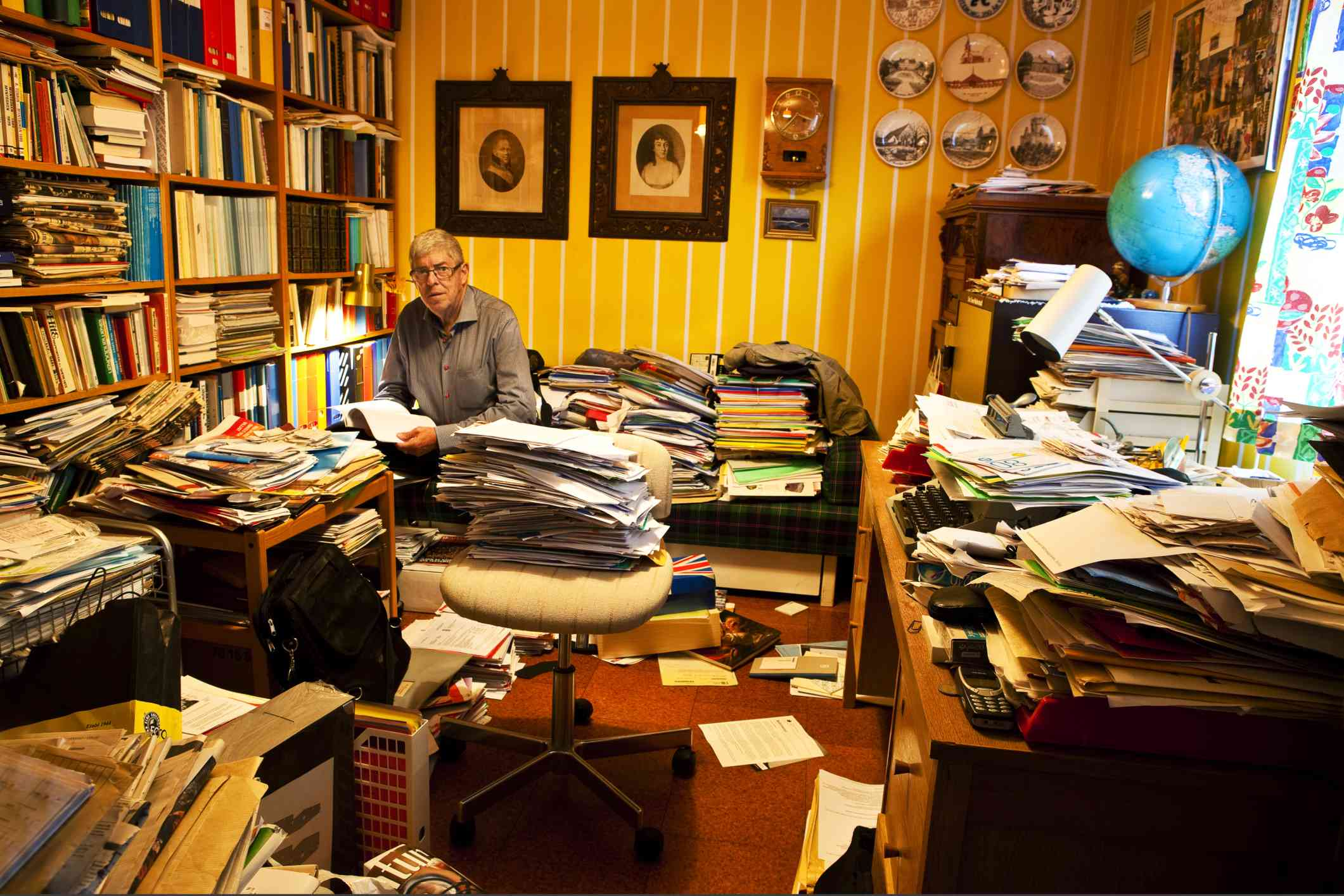 Man sitting in a room filled with clutter that he's hoarded
