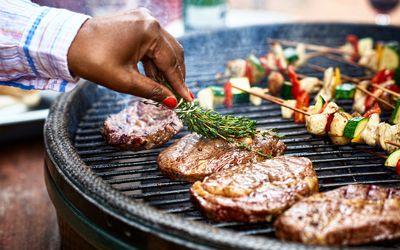 Woman seasoning beef on the BBQ