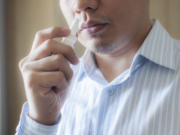 A patient is using a nasal spray
