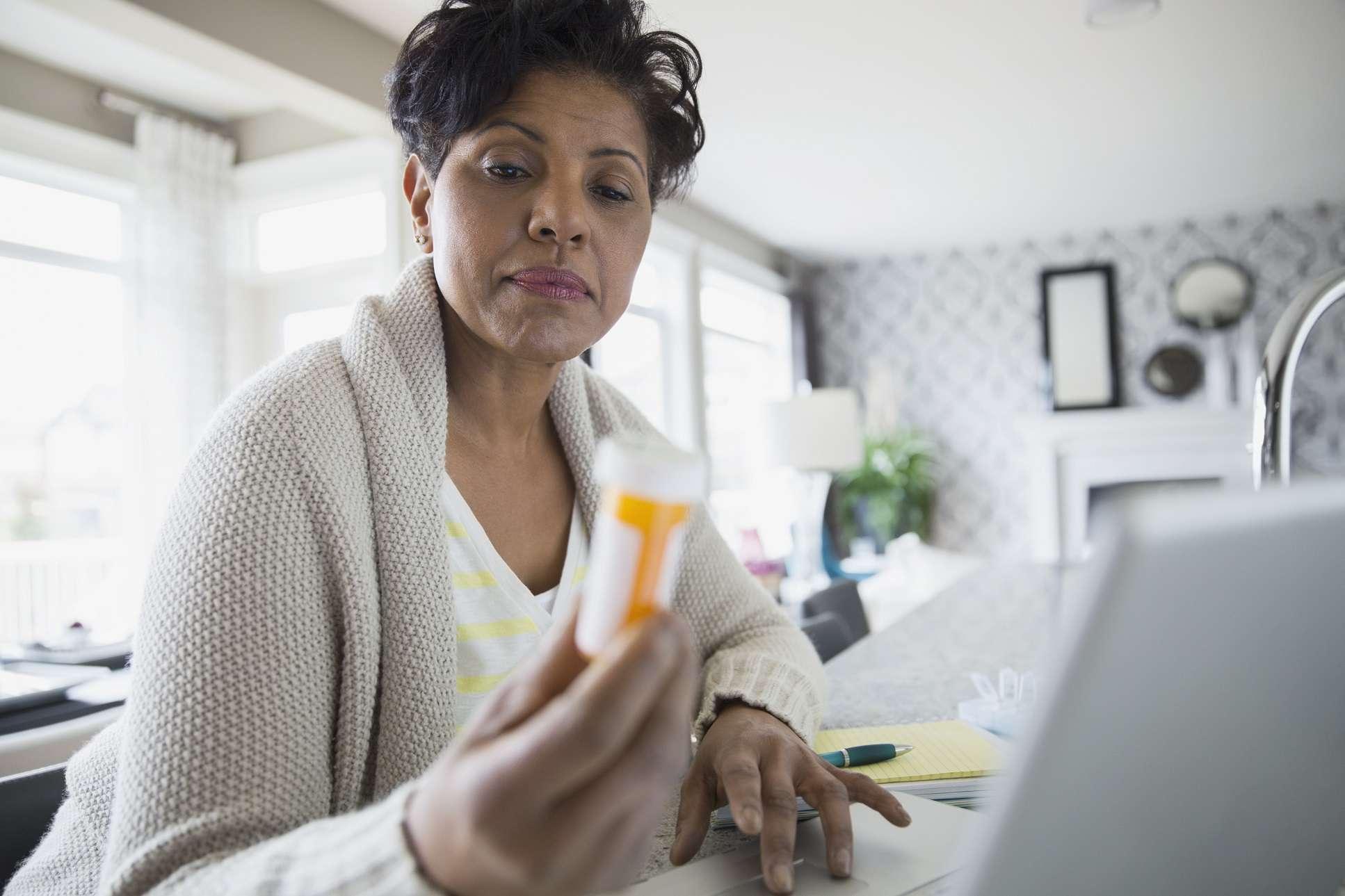 Older black women looking at a prescription drug bottle.