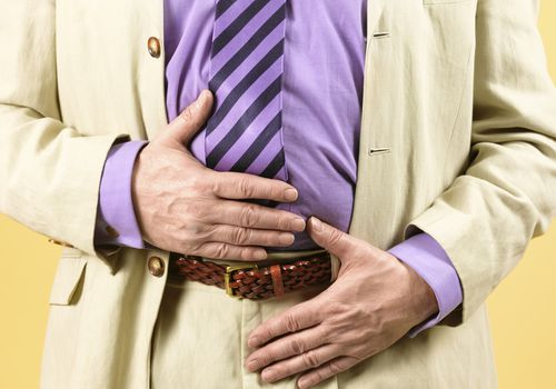 Man in a suit with hands over his stomach