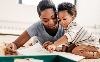 A black mom and a toddler reading a book