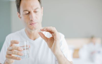 Man holidng a pill and a glass of water