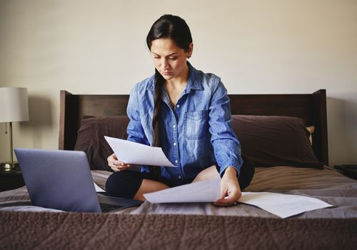Woman sitting on a bed with paperwork and a laptop computer.