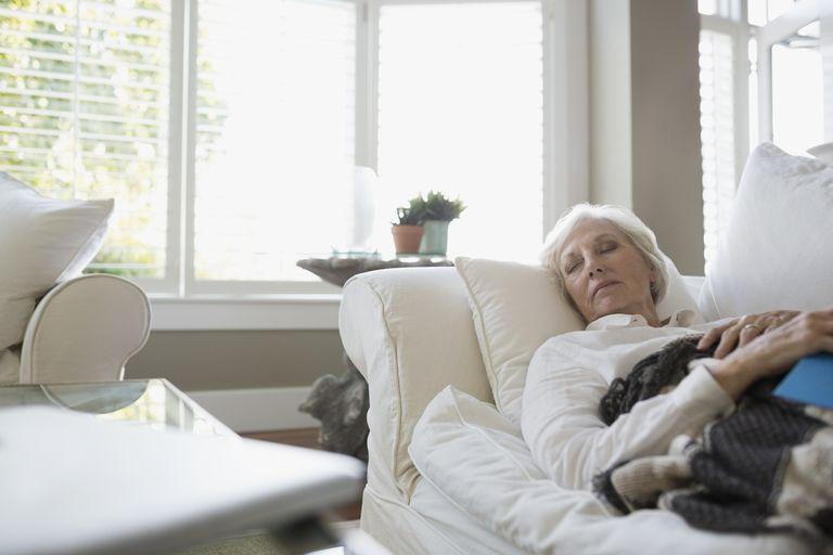 Tired senior woman napping on living room sofa - stock photo