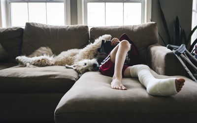 Boy with a cast on his leg sitting on the couch reading with his dog