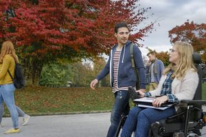 Man walking with a disabled woman on campus