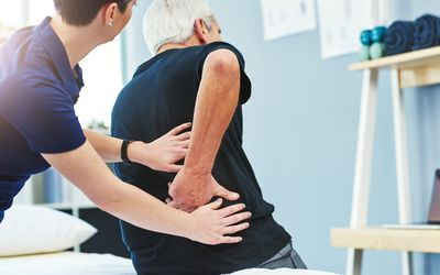 Doctor examining patient's back pain