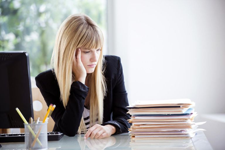 Businesswoman looking at stack of files